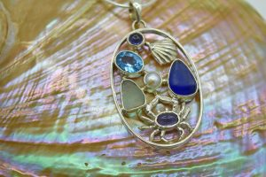 Sea glass, crab, blue topaz, and iolite pendant